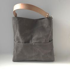 A casual, gray tote bag crafted from canvas that has been waxed with pure filtered beeswax and then sun-dried. Super durable, this waxed canvas bag will soften and become more creased and distressed w