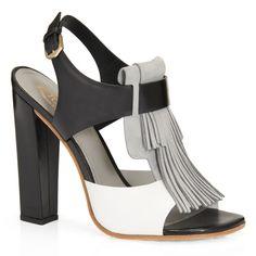 Sandalia en valiosa piel semibrillante combinada con el aterciopelado nobuk del maxi fleco frontal, con cinturón en el tobillo, tacón revestido y suela de cuero con gomminos en relieve.