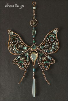 """So sparkly and pretty for your window!!!  Filled with beautiful Natural Gemstones in Ocean Blues / Greens and wrapped in Bronze to create this very pretty """"Silk Moth"""" Suncatcher.  Gemstones consist of... Seafoam Chalcedony, Neon Blue Apatite, Aqua Apatite, Green Onyx, Fluorite, Topaz, and Aquamarine.  Soldered and Wire Wrapped in Raw Bronze Oxidised, Waxed and Polished for a lovely soft antique Patina  Measures 20cm (8"""") in length and width is 10.5cm (4.2"""")  Comes with a window suction hook…"""