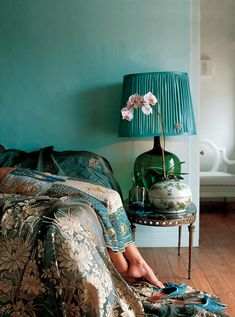 The single branch of orchids with the softest shade of pink becomes a striking focal point in this dark teal and green bedroom.