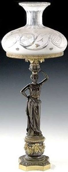 A sinumbra lamp probably manufactured by Messenger & Sons Birmingham, patinated bronze depicting a neoclassical maiden supported by a cylindrical pedestal decorated with applied ormolu festoons of flowers and grpaes raised on an octagonal plinth. Fuel reservoir has four feeder tubes with reticulated shade ring which supports a cut and etched blown peeriod glass globe with faceted neck and rim. England, circa 1825-1850