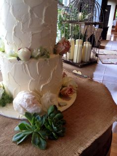 Wedding cake with succulents around the base and flowers bring the cake into the reception styling.