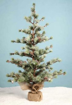Pine Tree In Burlap, by Bethany Lowe. Faux pine tree dotted with natural pine cones, with a burlap-wrapped base. This one stands 3 feet tall. Smaller version also available!