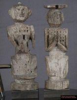 """Paire de statues représentant des idoles qui devaient se trouver dans un temple. Une des statue est assise les mains jointes en position de """"namasté"""" ce qui signifie: bonjour, au revoir, respect. on voit la tête du cheval au niveau de l'abdomen de la statue. La tête de la statue est ornée d'un toupet. Ces statues expriment une profonde humanité,  un grand calme et sont réalisées avec beaucoup de finesse. Elles proviennent de la région de Humla - Jumla au Nord ouest du Népal."""