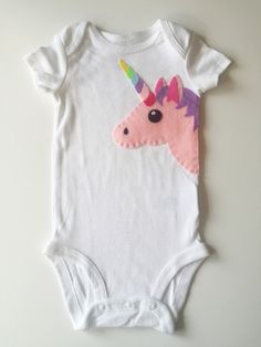 What is more magical and unique then a unicorn? Your little girl will sparkle in our handmade onesie/bodysuit/toddler shirt. .HANDCRAFTED. Every design I make is unique and handmade by me! Once you have chosen your desired colors, I hand stitch your custom design onto a high quality 100% cotton bodysuit/onesie. A lining is added on the inside of the item to preserve the stitching and protect babys skin. .ONESIE/SHIRT CARE INSTRUCTIONS. The felt we use for our appliques ...