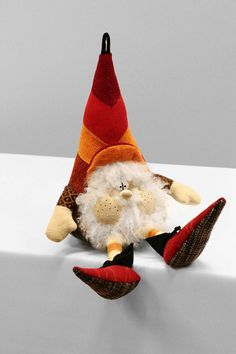 Cloth doll looks like Christmas gnome with brown, red, orange and rust chevron pattern hat and white beard. Ornament for tree or sit in unexpected spot for decor.
