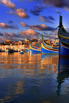 Colourful fishing boats called Luzzus float idly away in a bay in Malta.