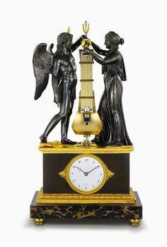"""""""Precision clock."""" With patinated bronzes by Pierre-Philippe Thomire representing Genius and Experience on black marble base, enamel dial with Breguet numerals, twin-barrel movement, constant-force escapement visible above dial, and rotating disc for seconds; 24 3⁄4 × 13 3⁄8 × 8 1⁄4 in. (62.9 × 34 × 21 cm). Sold October 22, 1806, to Mr. de Pourtalès for 3,000 francs. B453. Collection Montres Breguet S.A."""