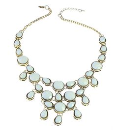 Modern and chic bib necklace adorned with multiple ivory stones in tear-drop and round shapes, all beautifully faceted to catch the lights.   Details: Chain Length: 18.5 in + 2