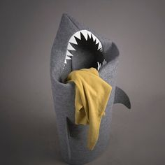 A shark that devours clothes...not people. Felt Shark Laundry Hamper might be placed both in the bathroom for laundry or in a child's room as a basket for toys. Also, thanks to its material, it might be squeezed behind something-for instance a washing machine-without losing none of its aesthetic valour.  Size/Dimensions/Weight 120 cm x 45 cm 47 inch x 17 inchMaterials: Gray and white 100% poliester felt.Production method: Handmade sewing. Please allow 2 weeks for shipping