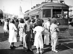 (ca. 1940s) - A group of people boarding the Pacific Electric Railway car in Hollywood for the Subway Terminal Building via Santa Monica Boulevard circa the 1940s.