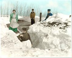 """~1913 Digging out after a three-day snowstorm  On roof of wooden house of James Ward having dug out from entrance after snowstorm. Snow is higher than roof of house. A shovel and stovepipe are visible. In the background is a line of trees.  """"Standing on the roof of the James Ward home, Milton, North Dakota, Mrs. James Ward, Nellie Ward, James Ward, Hugh Ward"""" James Ward  1850 Scotland d. 1911.  Wife Margaret Nielson 1859 iOntario, Canada. D.   1941 settled in Cavalier County, raised  6 kids."""