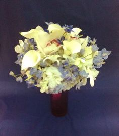White hydrangeas, calla lilies, dendribium orchids, and cymbidium orchids form the basis of this wedding bouquet. Light and bright blue delphinium provide a touch of contrasting color.  See more wedding bouquets, centerpieces, and more at www.jeffmartinsweddings.com