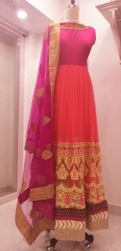 Pink tulle and raw silk bridal anarkali embroidered with beautiful off whit and pink floral motifs and sari borders at the hem.