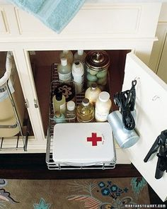 Sliding Trays - Central bathroom cabinets can be fitted with roll-out wire trays, the kind used in kitchens. One contains a first-aid kit and miscellaneous toiletries. A pair of hooks fastened to the inside of the door hold a hair dryer and a flat iron. In the adjacent cabinet, a second sliding track holds the bathroom's trash can.