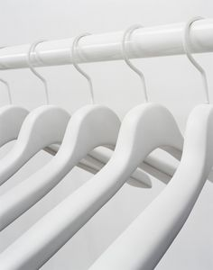 Chic, minimalist white hangers on a white clothing rail. Photograph by Edwin Himself.