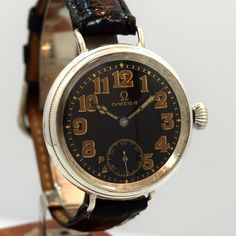 A vintage 1918 Omega Sterling silver watch with a black dial, and rust/gold-color Arabic numerals. This timepiece features a 35mm wide case, and a hand-made black, French Crocodile watch strap. In 1918, Omega watches were used by both, British and American aviators whilst at war with the Central Powers in WWI. (Store Inventory # 9940, listed at $1950).