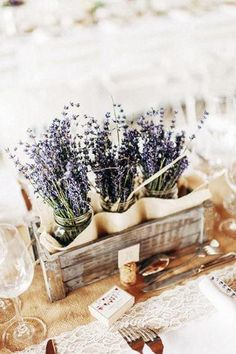 Disguised jars in wooden crates house a bundle of wild lavenders, lending a warm and bucolic touch to the table.