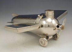 A.J.A. Henckels - DescriptionChrome plated smoker's set in the form of an aeroplane. Match compartment with ribbed top to cap, removeable disc shape box enclosing two ashtrays, the body of the plane with hinged cover for cigars, cigarette cases as removeable wings, the propeller as cigar cutter, the wheels slide off to reveal small empty compartment.
