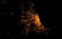 """Chicago, Illinois - captured at night from the International Space Station - is constructed on the southwestern shore of Lake Michigan. When the city was founded in 1833, most of the early construction radiated from the mouth of the Chicago River and its central, built-up areas remain relatively consistent with the natural flatness of the surrounding geography. This photograph is courtesy of NASA's """"Cities at Night"""" project"""