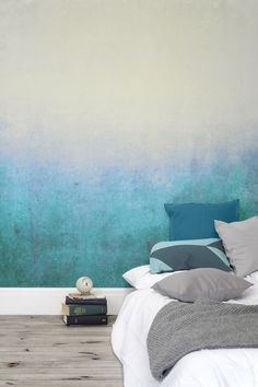 Deep blues gently fade into green tones. This subtle ombre wallpaper design creates a soothing atmosphere.
