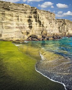 Puu Mahana Beach, or Green Sand beach, on Hawaii's Big Island is tinted green due to a large portion of polished olivine crystals, a byproduct of cooling lava, in the sand.