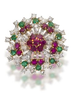 A diamond, ruby and emerald pendant/brooch, Tiffany & Co.  the circular panel centering a cluster of circular-cut rubies within a radiating surround of baguette, marquise and round brilliant-cut diamonds, circular-cut rubies and circular-cut emeralds; signed Tiffany & Co