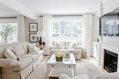 Open concept living/dining room with custom upholstered sofas, natural fibre rug, custom drapery and cushions. Designed by Lux Decor, Pointe-Claire, Qc