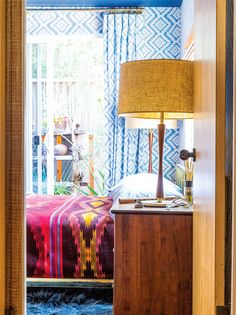 Printed blue curtains, printed purple blanket, wood nightstand, brown lamps, and blue rug