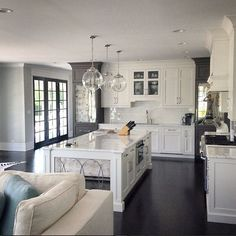 White and gray kitchen. White kitchen cabinets with kitchen island featuring antique mirror on sides. #WhiteKitchen #WhiteandgrayKitchen #MirrorIslandKitchen A. Perry Homes.