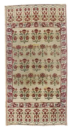 Ottoman velvet panel, Turkey, 17th/18th Century, of rectangular form, decorated with red and green voided velvet threads on a cream ground, with stylised floral stems, possibly roses or carnations, the border with a similar floral vine, each end with framed foliate designs, 130 by 66cm.
