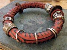 Celie Fago: carved bracelet with embellishments: polymer clay, fine silver, sterling, 18k gold, rusted steel