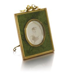 A Fabergé Imperial gold-mounted hardstone frame, workmaster Michael Perchin, St Petersburg, 1899-1903, the nephrite panel within a border of two-colour gold entrelac with fleuron corners, the oval aperture with beaded bezel, ribbon tie surmount, ivory back, containing an albumen print of Grand Duke Michael Nikolaevich.