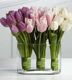 DIY Floral Arrangement bunches of leaf-wrapped tulips in clear vase
