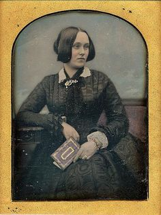 """Be-hold photographs: """"Collector's Joy."""" PLATE DAGUERREOTYPE BY BARETT & STANLEY. A portrait of a woman who holds a book with a decorated cover. The cover is gilded and the hand that holds the book shows off a gilded and red bracelet. There is other coloring. The ¼ plate daguerreotype is housed in a full case with a rich gilded logo on the cover for Barrett & Stanley. This partnership started in Dublin in the 1840's, and was in London during the 1850's."""