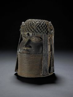 Cast bronze tusk-stand in the form of a human head.  The eyes are inlaid with iron.