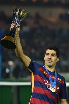 Luis Suarez of FC Barcelona celebrates with the trophy during the final match between River Plate and FC Barcelona at International Stadium Yokohama on December 20, 2015 in Yokohama, Japan.