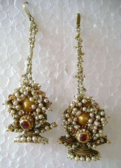 These are earrings from Karnataka, India from the 1800s or 1900s. They are made of gold, probably 22k, pearls, lac, which is a natural material often used to stabilize repouse, and red stones, likely rubies. The ear post is down on the body of the earrings, and the chains are brought up to hook into the hairdo. This adds beauty and offsets the weight of heavy earrings.