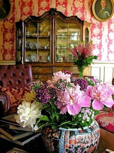 Love this room. Love the wallpaper and the yummy vase of flowers, and the cupboard full of majolica