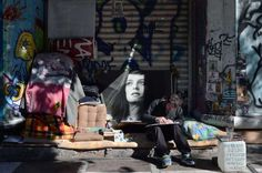 Un sintecho pinta cuadros en la calle para venderlos en el centro de Atenas, Grecia.