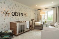 A Nursery Works Novella Convertible Crib sits on light gray rug under black wall letters flanked by Restoration Hardware Sputnik Filament Sconces illuminating a RH Baby & Child Oversized Wool Felt Giraffe on one side and a gray book rack on the other side.
