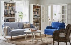 A light living room furnished with a light blue three-seat sofa and a blue armchair. Shown together with a round white coffee table and a rattan armchair.