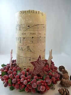 Vintage sheet music ModPodged to candle rolled in glitter and set in berry ring.