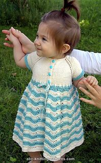 """This charming little dress was designed and knitted for my granddaughter. I called it the """"Best Sunday Dress"""" because it really seems to me just a little too fancy to wear everyday! It is knitted seamlessly from the top down. The top features comfy raglan-style sleeves. I debated between putting the buttons on the front or on the back, and decided to put them on the front for a more traditional look. The skirt is formed with repeats of a lace motif that gives it a wavy texture. It should be…"""