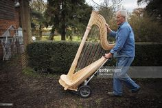 Harp maker John Hoare moves a Pedal Harp between workshops at Pilgrim Harps on November 25, 2010 in South Godstone, England. Using traditional crafts and techniques, Pilgrim Harps have been producing bespoke Pedal, Lever and Lap harps since 1980, and are one of the only remaining hand made harp producers left in the UK.