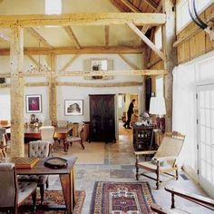 An old barn's siding and frame serves as paneling in this new house's great room and an old beam serves as a staircase banister.