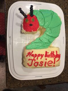 For my daughter's second birthday I created a Hungry Caterpillar cake in the shape of the number two. The eyes were made from yellow and green gummy candy (I used jelly fish because they were flat) and the mouth is one raisin. Antennae were toothpicks with blueberries. To make the cake, I did a simple sheet cake, cut in half and stacked to make a layer cake, and then cut around and removed the pieces to make a 2. Any number would do!