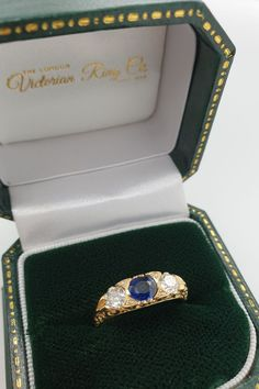 This sapphire and diamond ring is set with a centre blue sapphire with an old-cut diamond on either side. The 18ct yellow gold ring has four diamond points set between the sapphire and larger diamonds. This Victorian style ring is known as a carved half hoop design and is true to original 19th century rings. #LondonVictorianRing #HalfHoopRing #VictorianRingDesign #SapphireRing #SapphireHalfHoop #SapphireAndDiamond Engraved Wedding Rings, Country Rings, Victorian Engagement Rings, Full Eternity Ring, Jewelry Insurance, Three Stone Rings, Conflict Free Diamonds, Yellow Gold Rings, Beautiful Rings