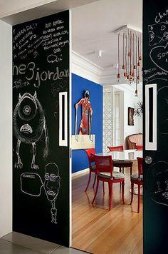 A porta de correr, entre a cozinha e a sala de jantar, foi pintada com tinta preta fosca. Por isso, pode receber desenhos e recados feitos com giz. Projeto do arquiteto Felipe Rio Branco