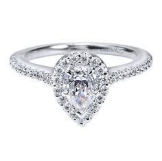 This lovely halo engagement ring features a pear shaped center stone surrounded by tiny diamonds. Pledge your eternal love and devotion with this 14K White Gold Contemporary Halo Engagement Ring.